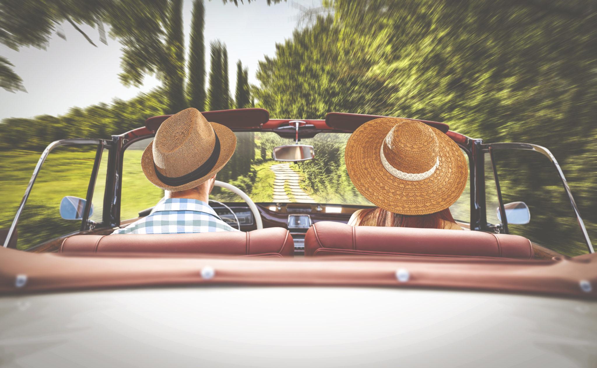Coppia in auto che percorre una strada di campagna