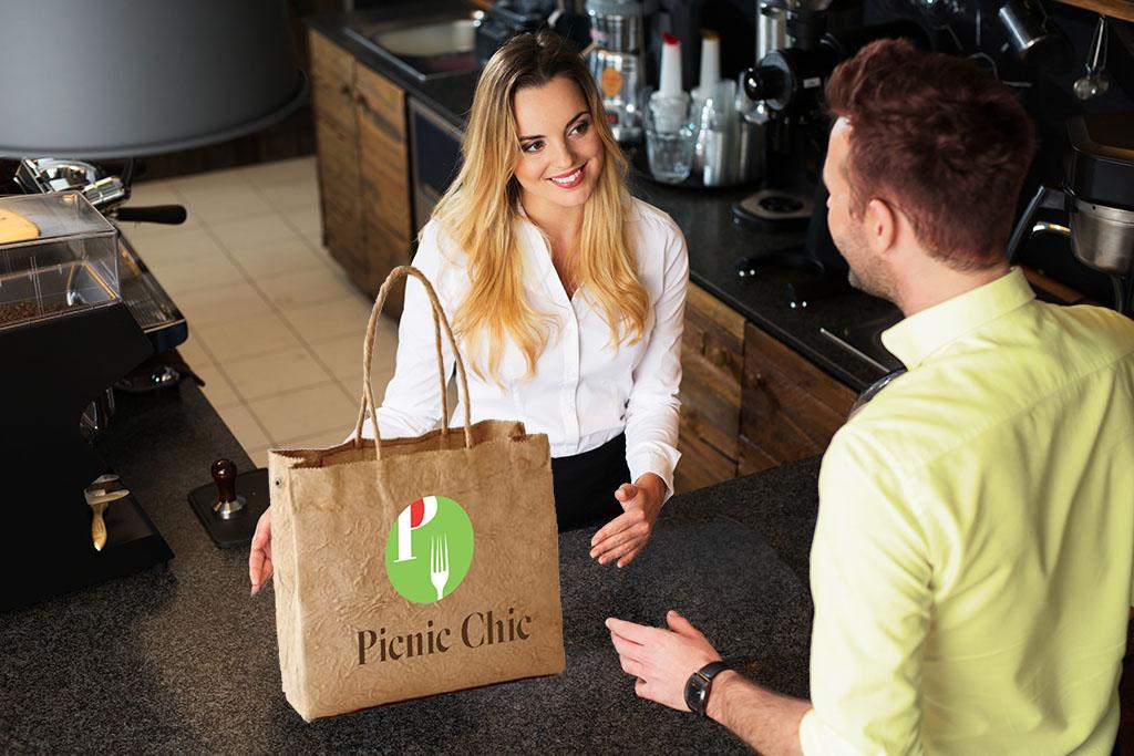 Commessa che porge la shopping bag al cliente