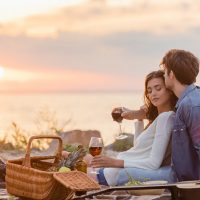 Selective focus of couple holding glasses of wine during picnic on beach at evening